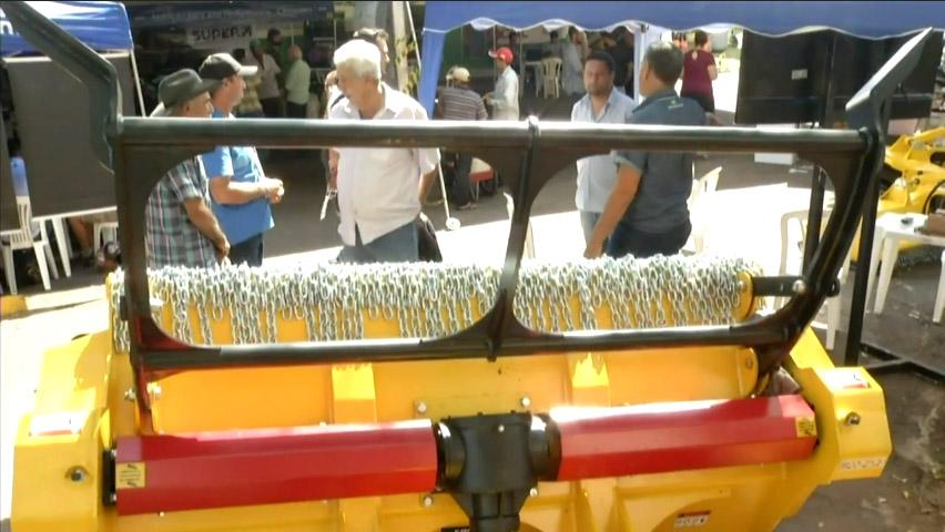 Equipamento Tritucap virado pra cima em exibição na feira e pessoas olhando